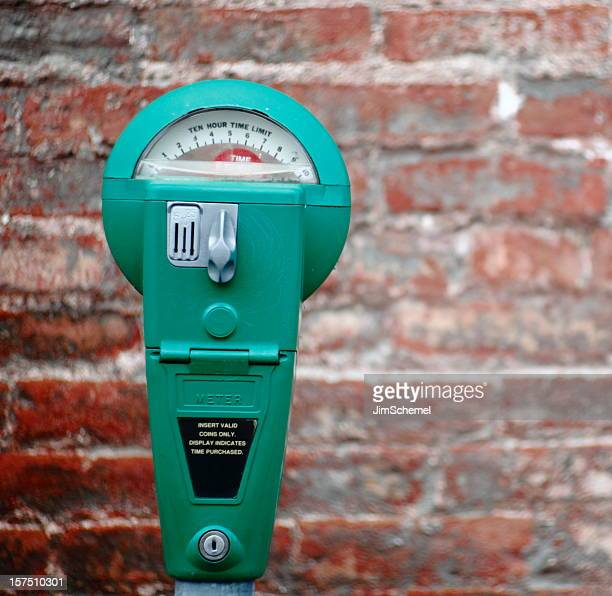 a bright green parking meter on a brick background - parking meter stock photos and pictures