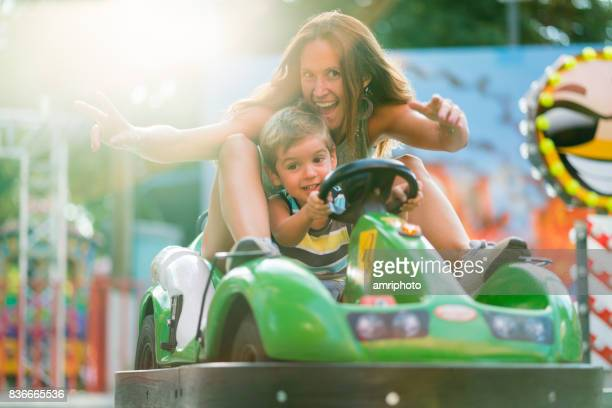 bright happy summer picture of mom and little son in amusement park