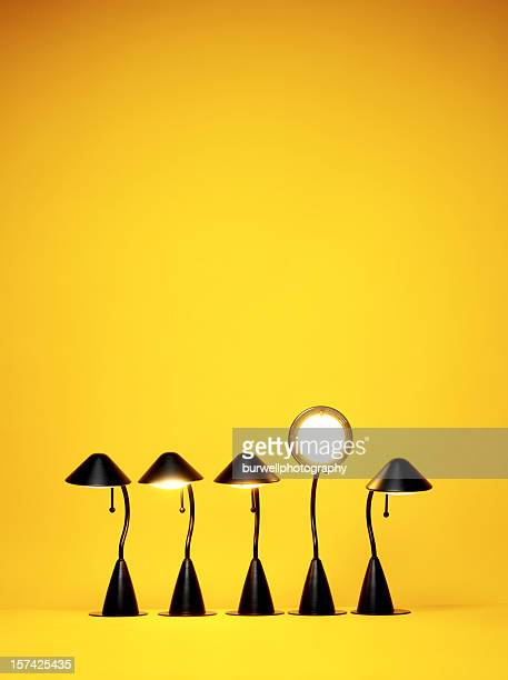 bright idea, five desk lamps against yellow - electric lamp stock pictures, royalty-free photos & images