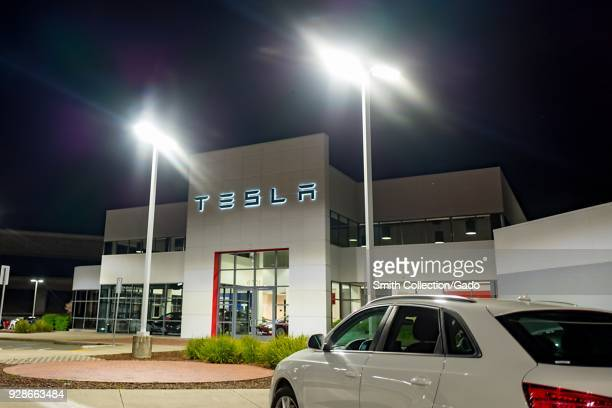 Bright lights illuminate a Tesla Motors dealership at night with automobile visible in the foreground Dublin California March 5 2018