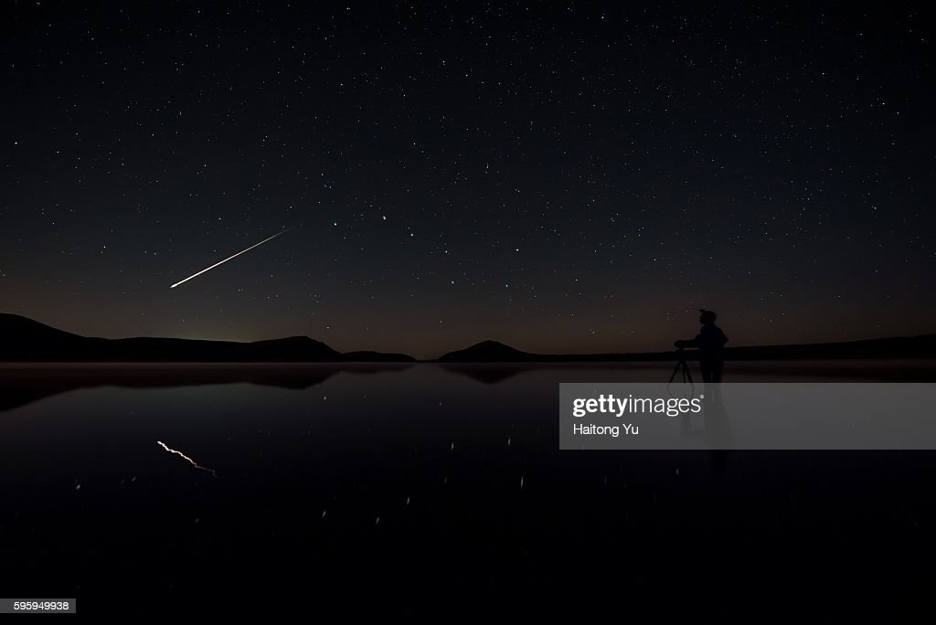 A bright meteoroid flying past as a man setting up his camera inside a lake : Stock Photo