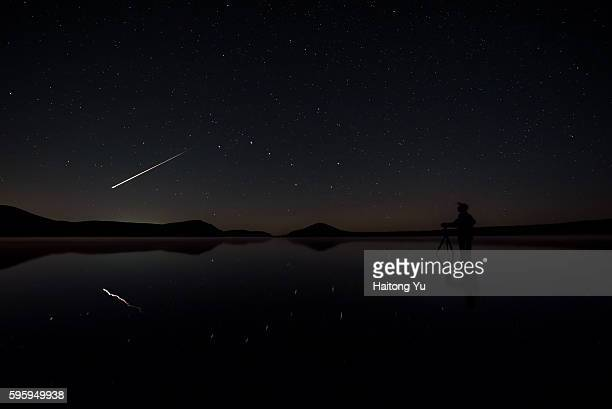 a bright meteoroid flying past as a man setting up his camera inside a lake - grande carro costellazione foto e immagini stock