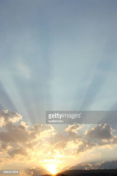 Bright morning sun rays peeking over clouds