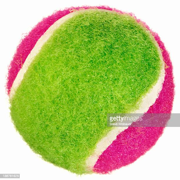 A bright neon pink and green tennis ball