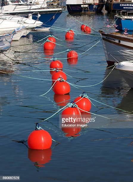 Bright orange mooring buoys in West Bay harbor Dorset UK