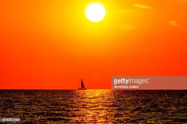 bright orange sunset over golfe de saint-florent, corsica, france - navigation de plaisance photos et images de collection