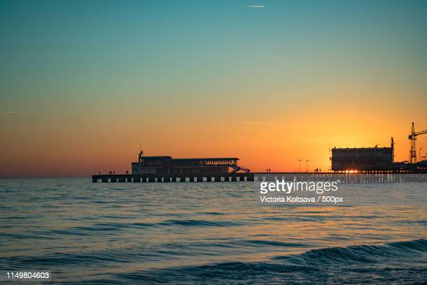 bright orange sunset over the sea pier of the city - sukhumi stock photos and pictures