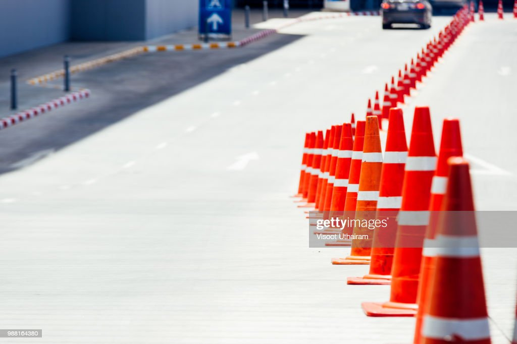 bright orange traffic cones standing in a row on asphalt. concrete sidewalk with yellow red and white traffic sign. : Stock Photo