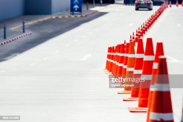 bright orange traffic cones standing in a row on asphalt. concrete sidewalk with yellow red and white traffic sign.