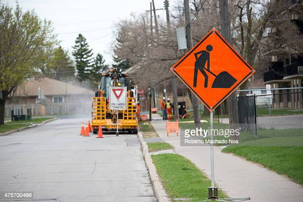 Bright orange traffic sign warns of construction ahead with construction equipment in the background