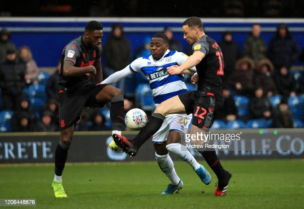 Bright OsayiSamuel of Queens Park Rangers is challenged by Bruno Martins Indi of Stoke City and James Chester of Stoke City during the Sky Bet...