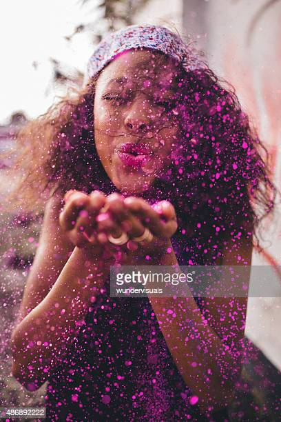 Bright pink glitter being blown by a teenage girl