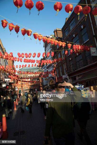 Bright red and yellow lanterns are strung across between the buildings creating a canopy of colour for Chinese New Year on Gerrard Street Soho also...