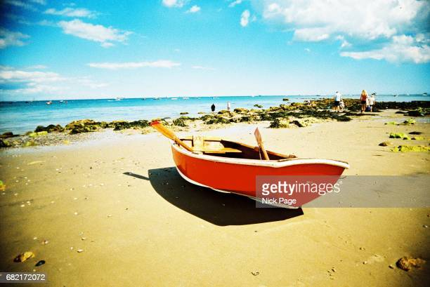 bright red boat resting on the beach - cross processed stock pictures, royalty-free photos & images