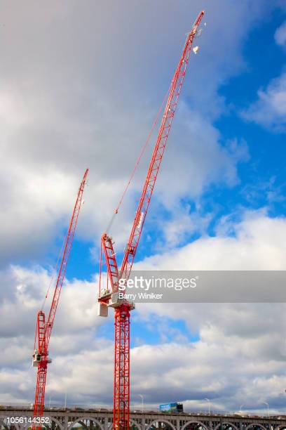 Bright red construction cranes against blue sky with patchy clouds