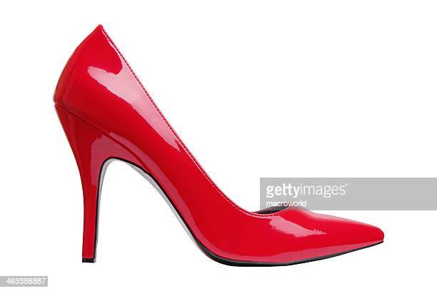 a bright red high heel woman's shoe by itself  - hoge hakken stockfoto's en -beelden