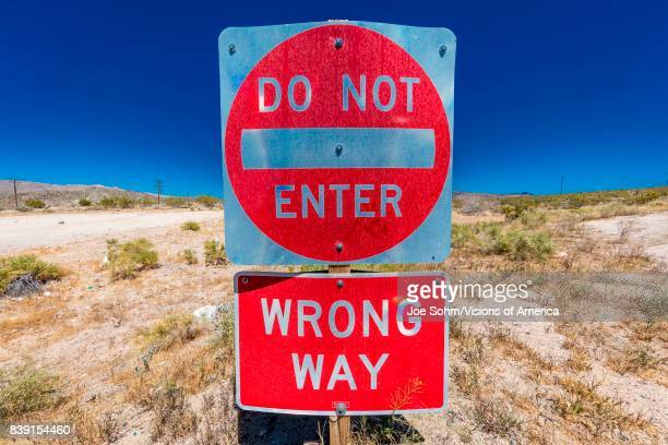 Bright Red sign warns drivers not to enter this lane of highway, Interstate 15, in desert outside of Las Vegas - WARNING - WRONG WAY!, Nevada.