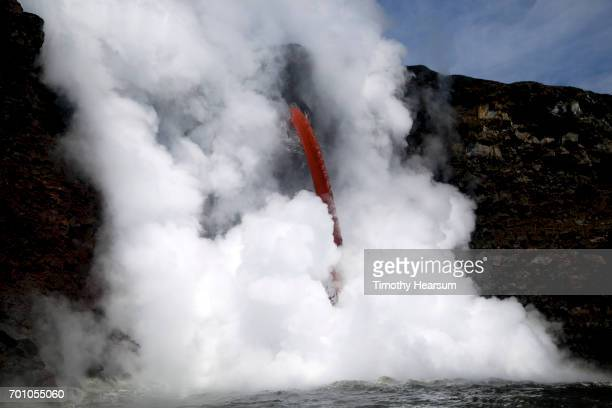 bright red tube of hot lava surrounded by steam pours into the ocean - timothy hearsum stock pictures, royalty-free photos & images