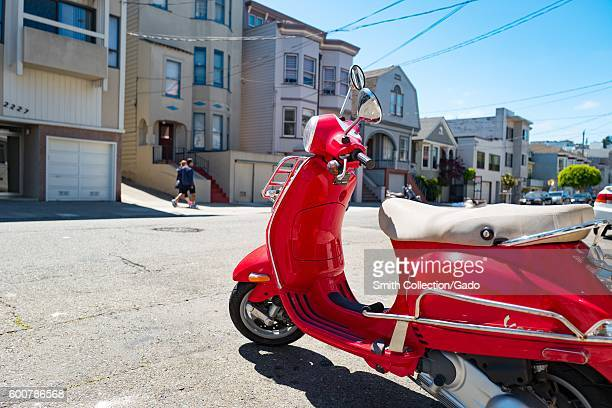 A bright red Vespa scooter parked on the street on a sunny day in the Cow Hollow neighborhood of San Francisco California August 28 2016