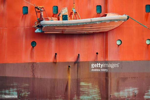 bright safety orange icebreaker ship hull and rescue dinghy lifeboat speedboat - lifeboat stock pictures, royalty-free photos & images