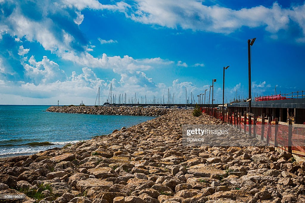 Bright sea pier  with colorful clouds over azure waters : Stock Photo