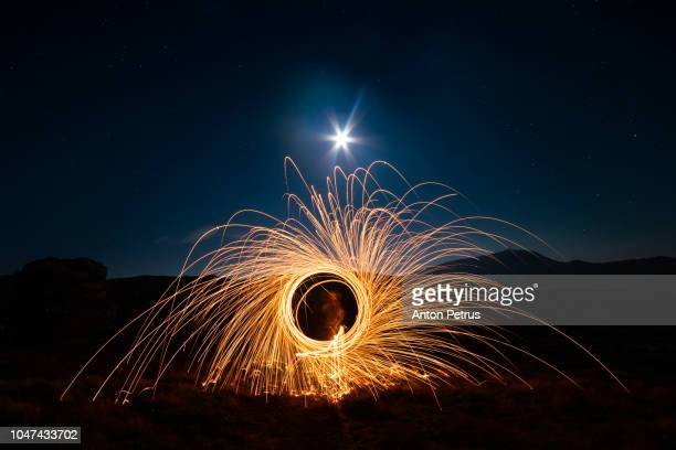 bright sparks at night in the mountains. fire show of steel wool - arte, cultura e espetáculo imagens e fotografias de stock