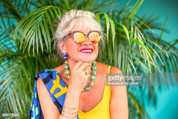 A bright stylish 66 year old seniors lady in a daylight studio.