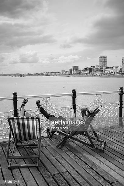 Bright summer day with two lads relaxing on Brighton pier in deck chairs