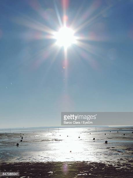 Bright Sun Shining Over Sea Against Blue Sky
