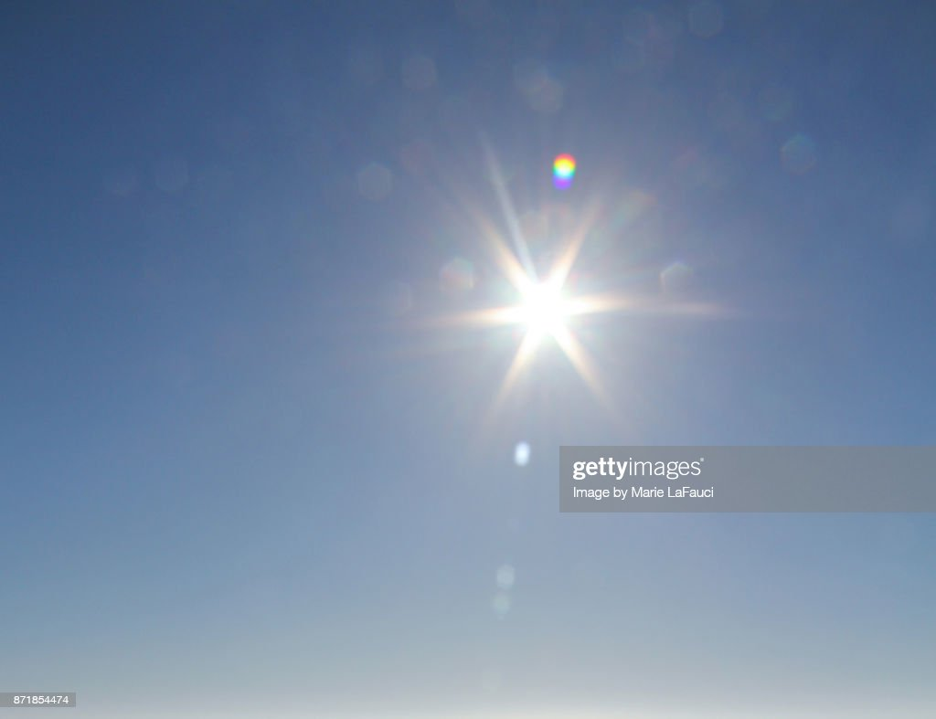 Bright sunshine glare against blue sky : Foto de stock