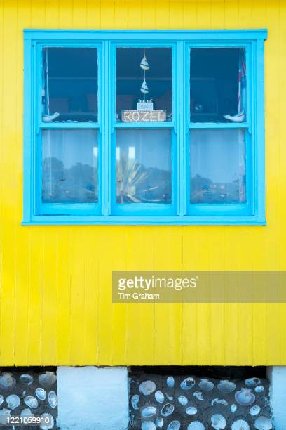 Bright yellow and blue painted beach hut seaside home in the resort of Rozel in St Martin region of Jersey Channel Isles