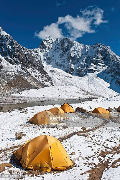 Bright yellow expedition dome tents snow mountain camp Himalayas Nepal