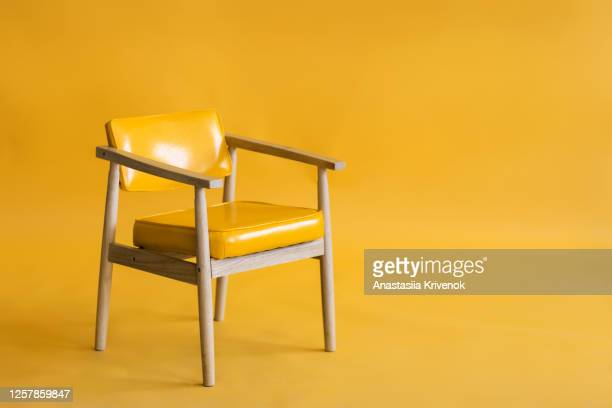 bright yellow leather and wood armchair is standing in an empty yellow background. concept of minimalism. - chair stock pictures, royalty-free photos & images