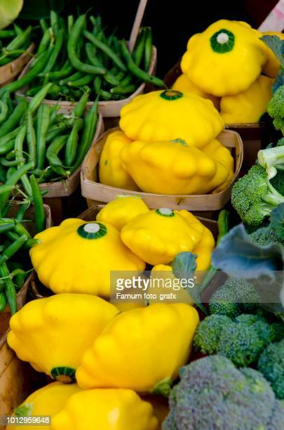 Bright yellow pattypan squashes between broccoli and mange tout
