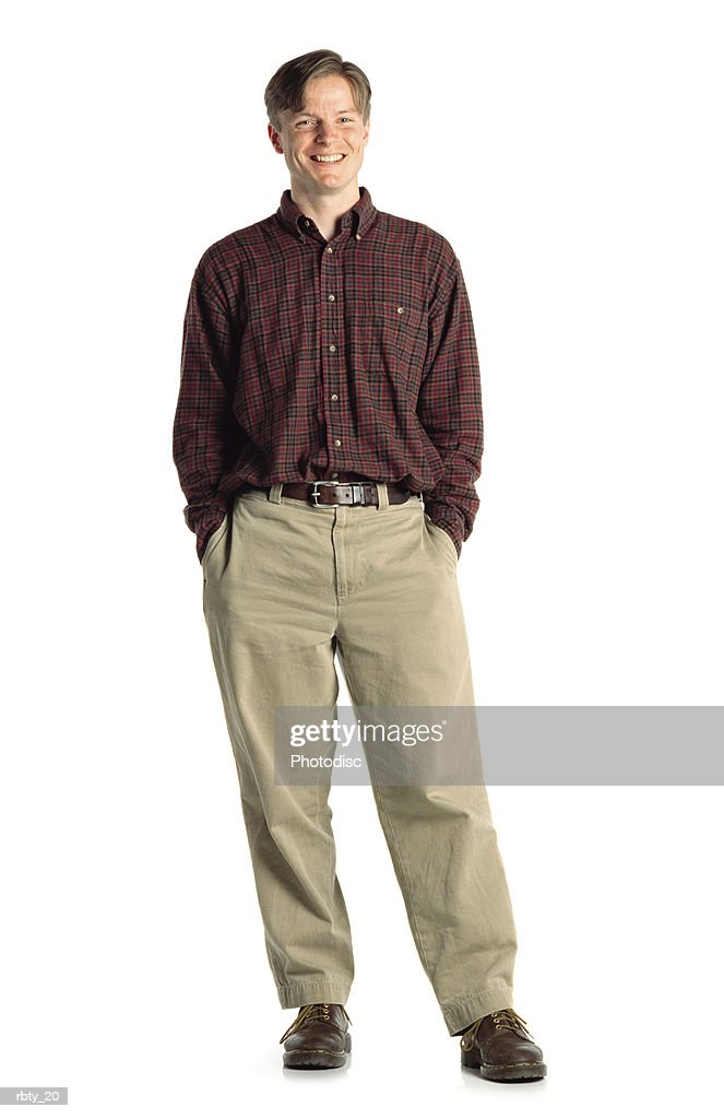bright young caucasian male wearing a red plaid shirt and tan pants stands with shifted weight and smiles : Foto de stock