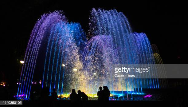 brightly and colorfully lit fountain - fountain stock pictures, royalty-free photos & images