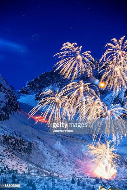 De brillantes coloridos fuegos artificiales de la noche de invierno paisaje de montaña