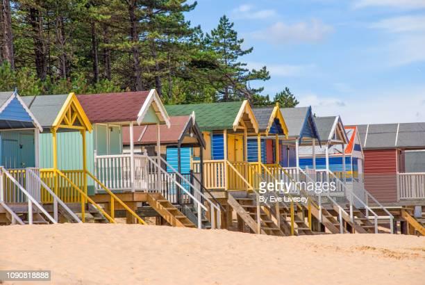 brightly coloured beach huts side view - norfolk east anglia - fotografias e filmes do acervo