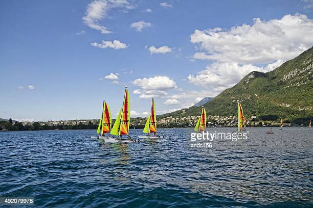 brightly coloured sailing boats on blue lake - lake annecy stock photos and pictures