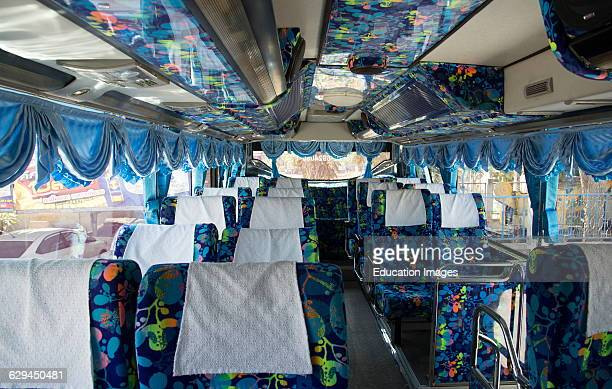 Brightly decorated interior of a tourist bus Thailand