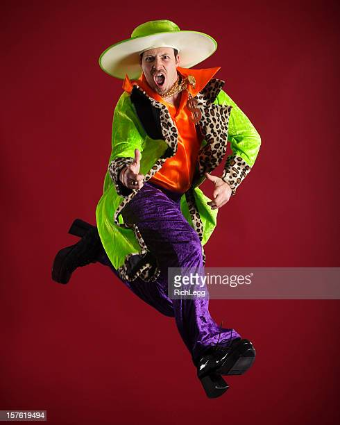 brightly dressed man in mid-air - purple shoe stock pictures, royalty-free photos & images