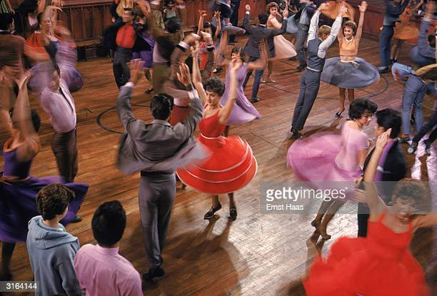 Brightly dressed young women and their partners in a lively dance scene from 'West Side Story' Rita Moreno and George Chakiris are amongst the couples