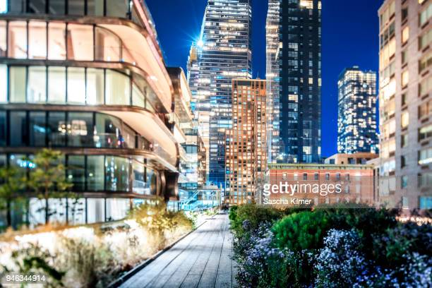 brightly lit buildings along the high line at night - chelsea new york stock pictures, royalty-free photos & images