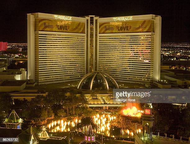 A brightly lit Mirage Hotel located on the famed Las Vegas Strip and featuring an erupting volcano is seen across the street from the Venetian Hotel...