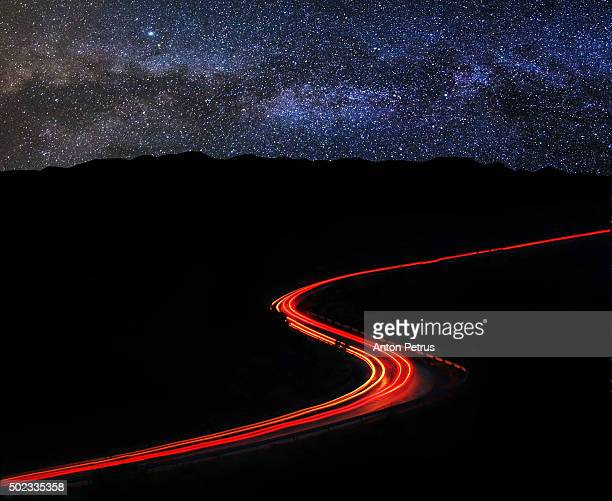 Brightly lit road at night along the mountain