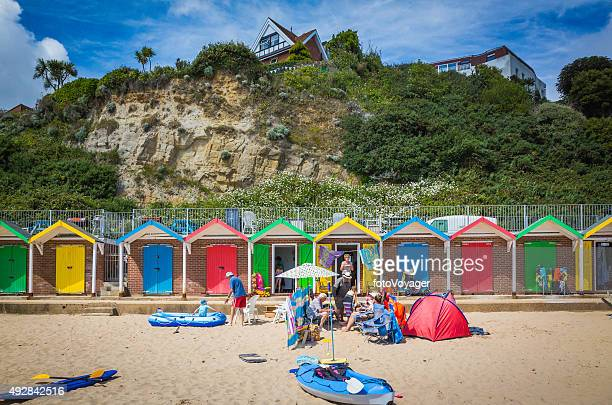 Brightly painted beach huts and families enjoying seaside sunshine England