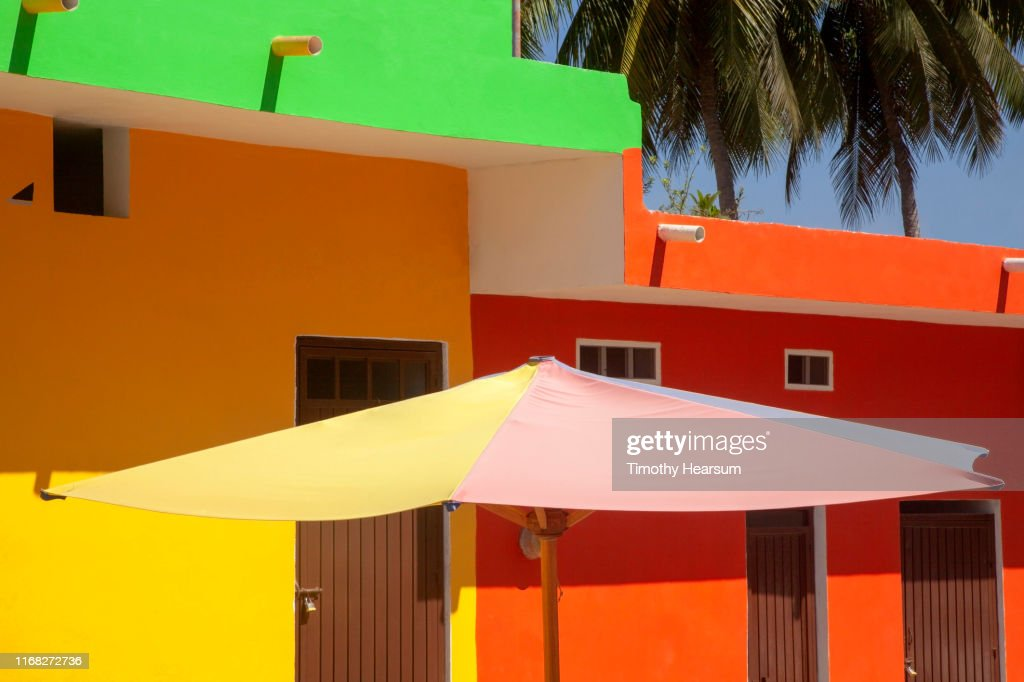 Brightly painted building with colorful umbrella; palm trees in background : Stock Photo