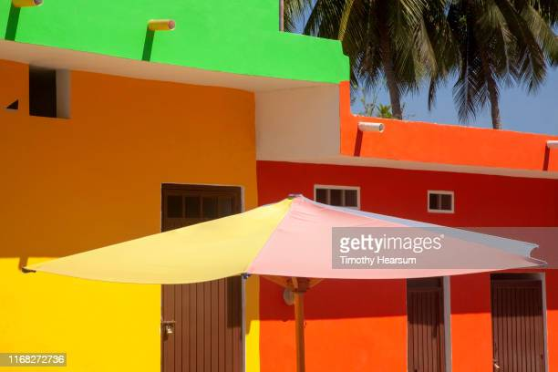 brightly painted building with colorful umbrella; palm trees in background - timothy hearsum stock-fotos und bilder