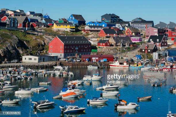brightly painted houses and boats in the harbor of ilulissat, greenland - ilulissat stock-fotos und bilder