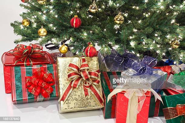 Brightly Wapped Christmas Gifts Under Tree Decorated With Ornaments